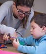 Support worker doing craft with boy