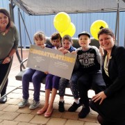 (L) Team leader, Amanda Daniels along with children supported by Identitywa receive the 'cheque' from Riverton CBA branch manager, Belinda Kyle.