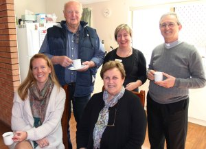 Father Nino enjoying a cup of tea with staff and an Identitywa family.