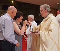 Genevieve receives Communion from Bishop Sproxton