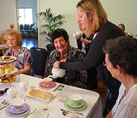 Identitywa staff member serving tea to carers