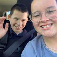 Lochie and his Identitywa support worker in Abi's car