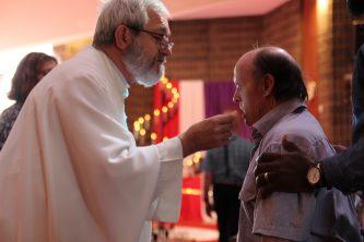 Man receiving Communion at Identitywa Easter season Mass